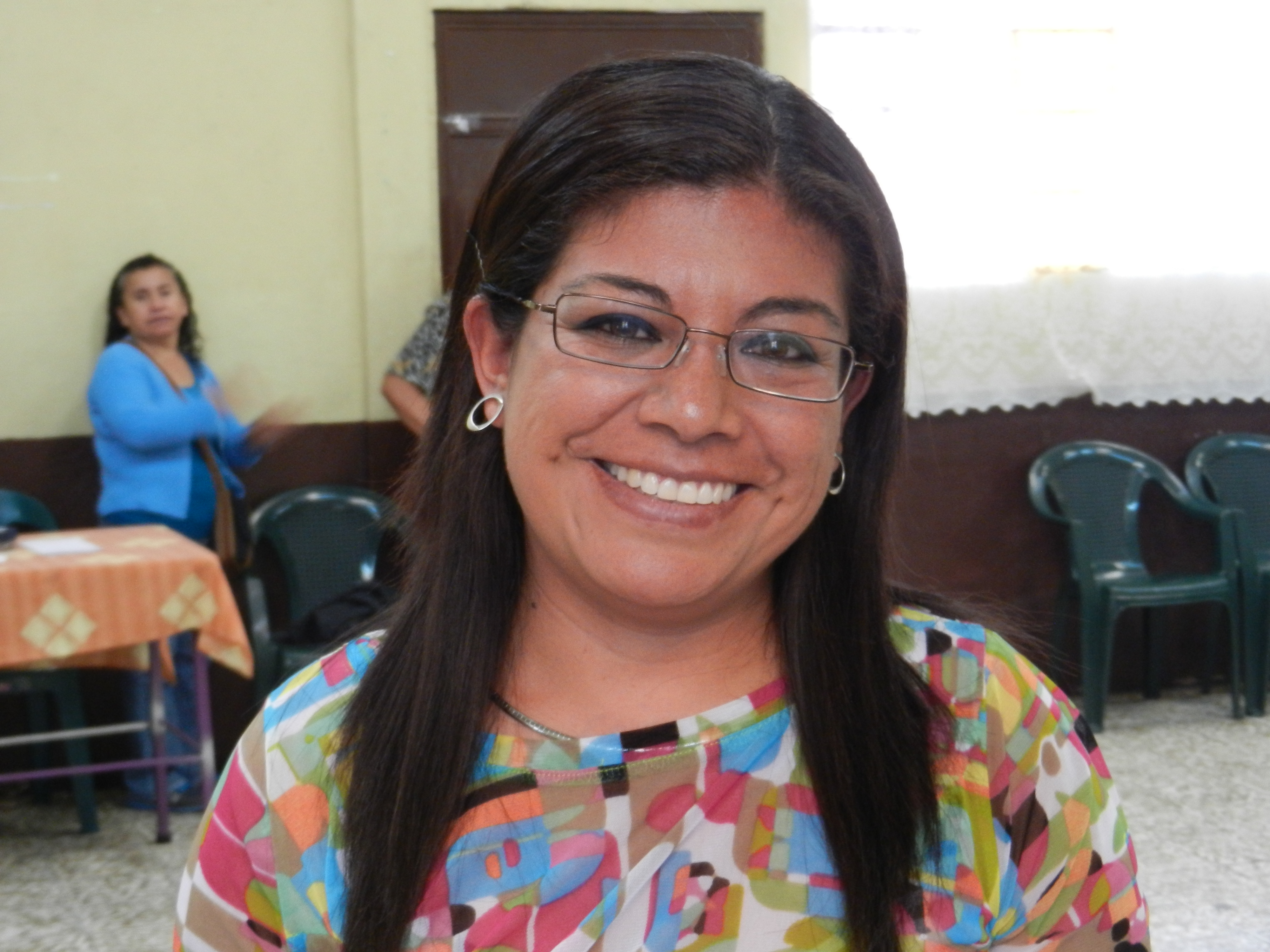 A woman smiling brightly with her new eyeglasses.